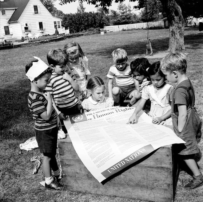 Photo en noir et blanc de 1950. Des enfants des membres du personnel des Nations unies regardent attentivement une grande affiche de la Déclaration universelle des droits de l'Homme.