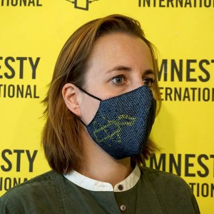 Femme portant un masque d'Amnesty International Luxembourg